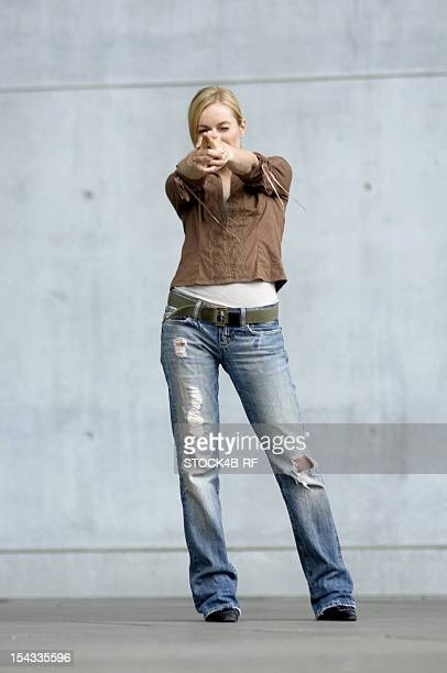 Young woman aiming with outstretched arms