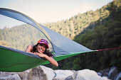 Young Woman Alone in Tree Tent, Smiling