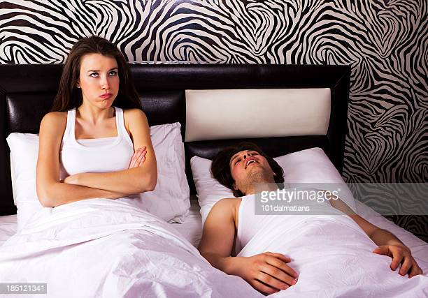 Young woman and a snoring man in bed