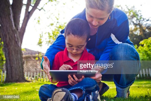 A young woman and boy using a tablet PC outdoors : Stock Photo