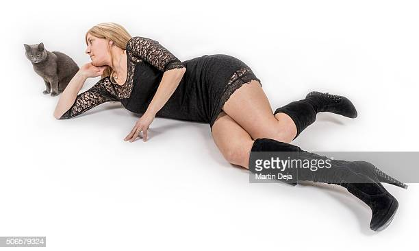 Young woman and cat lies on a floor and smiles