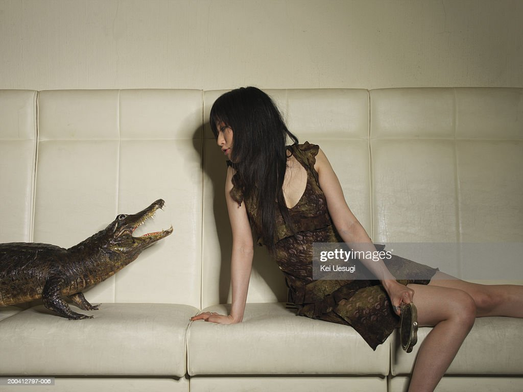 Young woman and crocodile sitting on sofa : Stock Photo