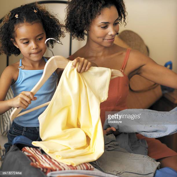 young woman and daughter unpacking clothes