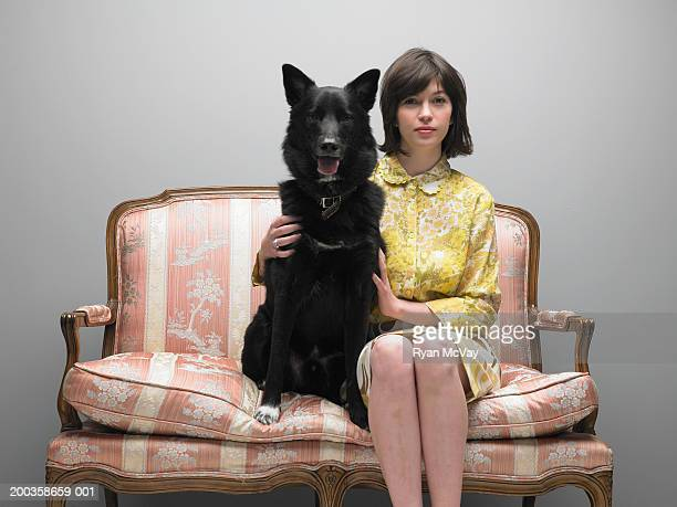 Young woman and dog sitting side by side on love seat, portrait