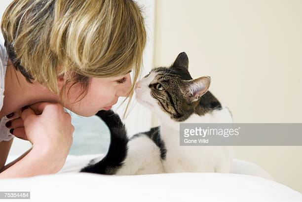 Young woman and domestic cat touching noses, side view, close-up