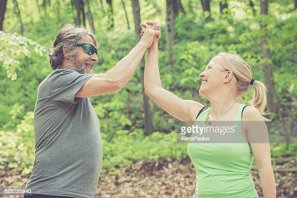 Young woman and elderly man in the forest, high five