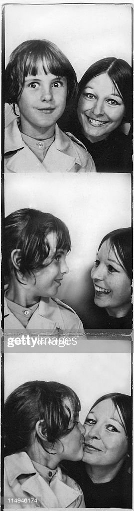 Young woman and girl in photo booth : Stock Photo