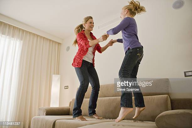Young woman and girl jumping on sofa