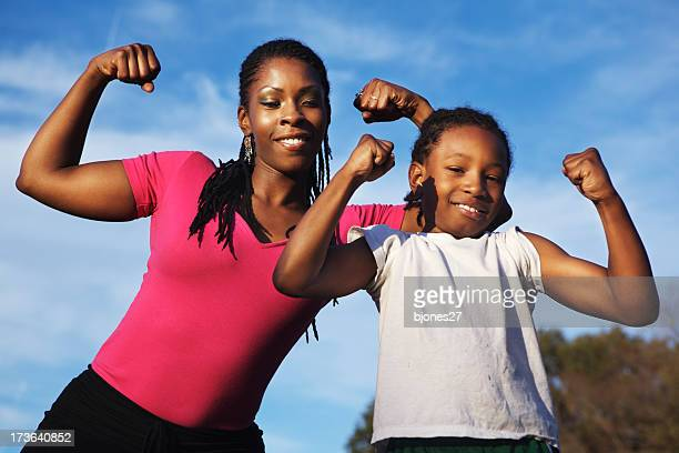 Young woman and girls showing of their muscles