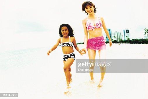 Young woman and Hawaiian girl walking in shallow waters : Stock Photo