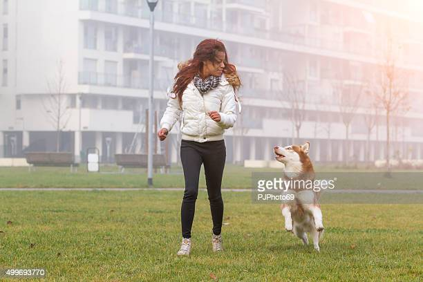 Young woman and her dog running and playing