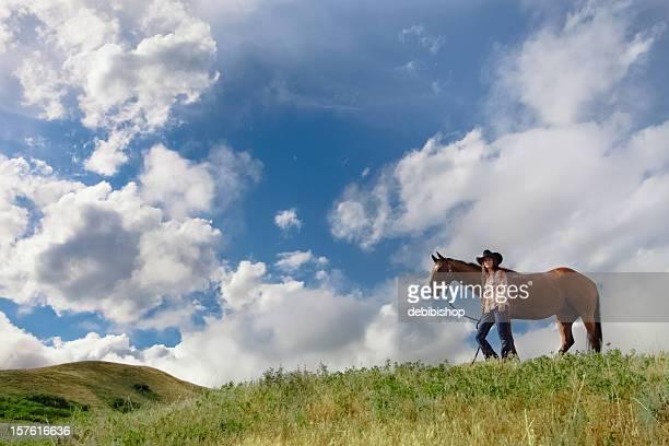 若い女性と彼女の馬の丘の上に