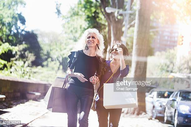 Young woman and her mentor shopping and laughing on street, New York City, USA