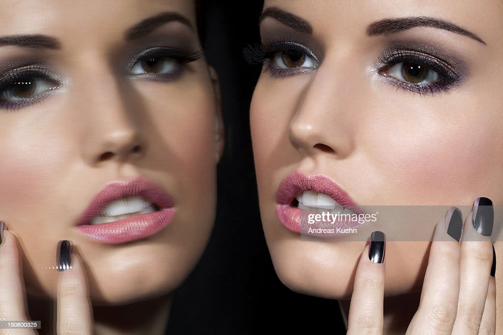 Young woman and her mirrow reflection, close up. : Stock Photo