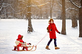 Young woman and her toddler son having fun in winter, focus on child