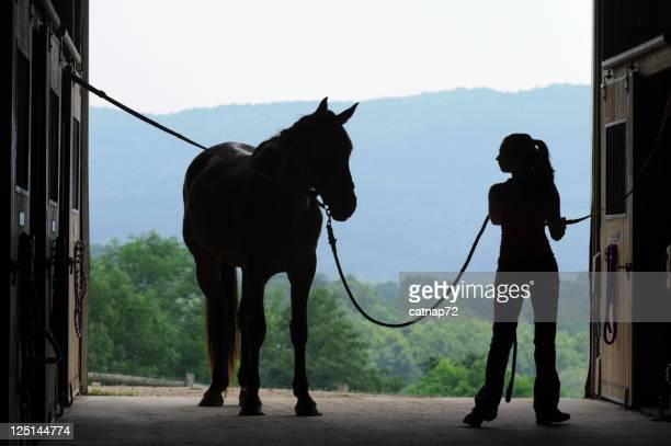 Young Woman and Horse Silhouette in Open Barn Door