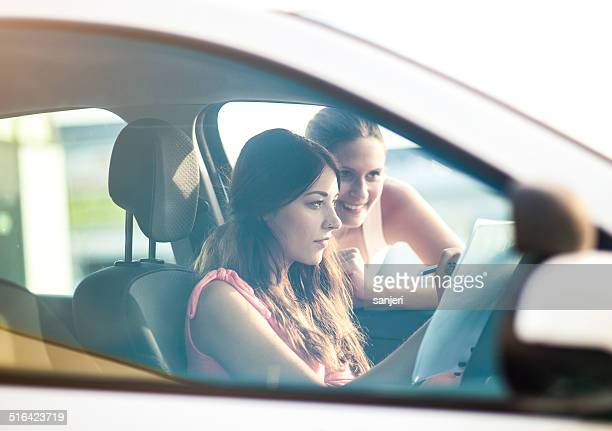 Young woman and instructor by the car