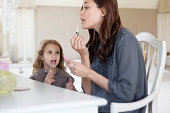 Young woman and little girl applying lip gloss at dressing table