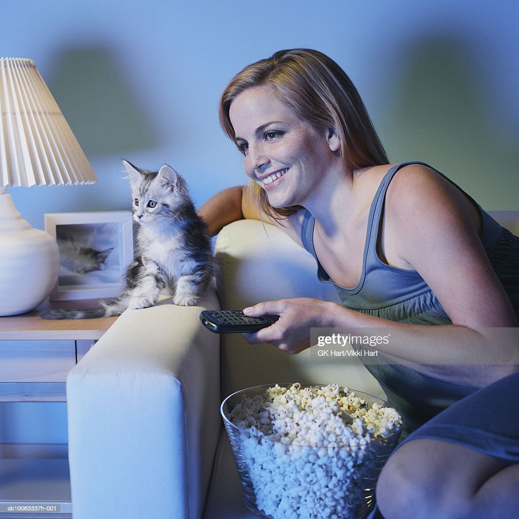 Young woman and Maine Coon Kitten watching television : Stock Photo