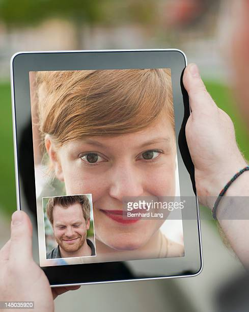 Young woman and man communicating via tablet