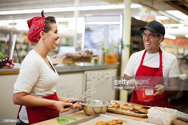 Young woman and man laughing in commercial kitchen
