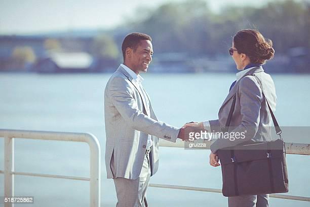 Jeune femme homme rencontre et se serrant la main au bord de l'eau