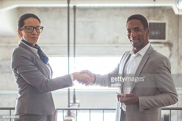 Young woman and man shaking hands in modern office space