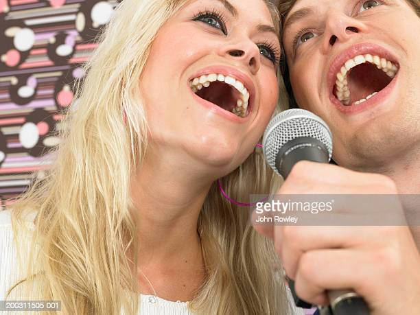 Young woman and man singing into microphone, low angle view