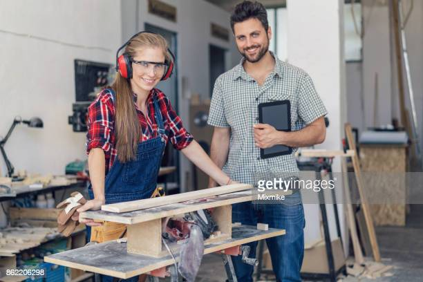 Young woman and man standing at the grinding machine in the carpenter workshop