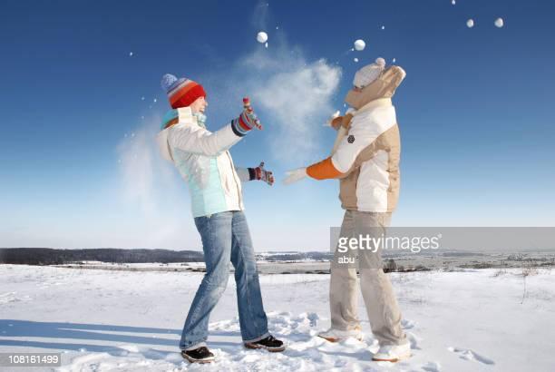 Jeune femme et homme jeter des boules de neige à l'extérieur