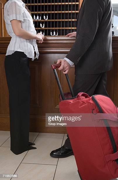 Young woman and man with luggage standing at reception desk in hotel