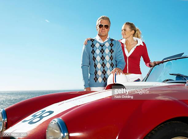 Young woman and mature man by classic racing car on coast