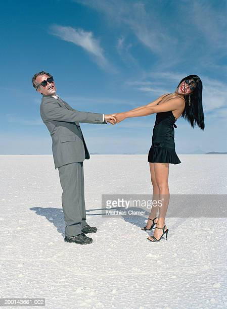 Young woman and  mature man holding hands(Digital Composite)