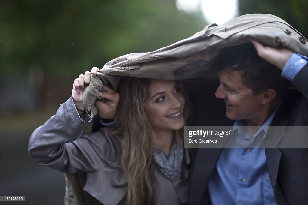 Young woman and mature man walking in park : Stock Photo