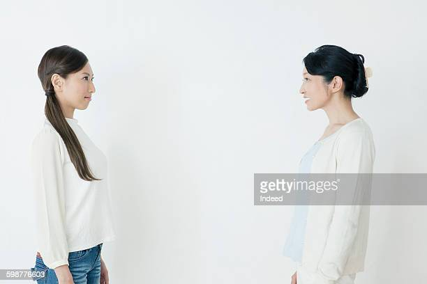 Young woman and mature woman looking face to face