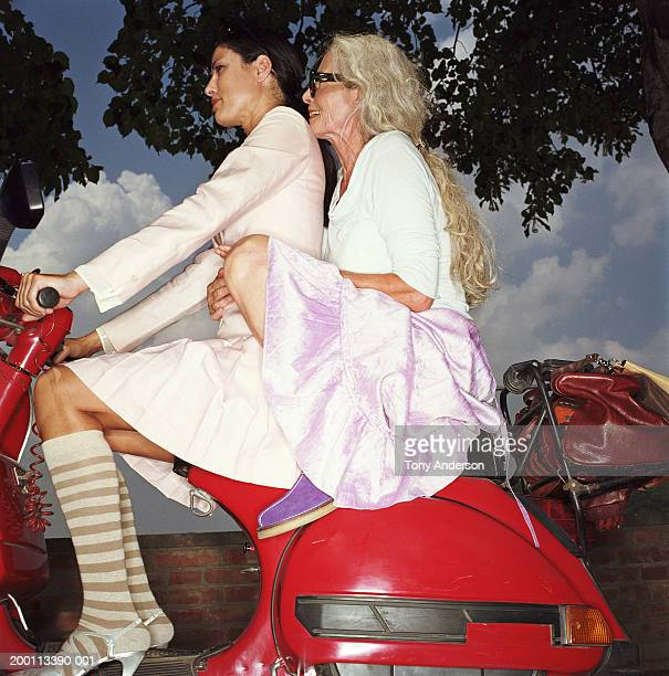 Young woman and mature woman on scooter, side view
