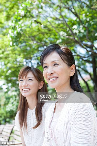 Young woman and mature woman smiling on bench