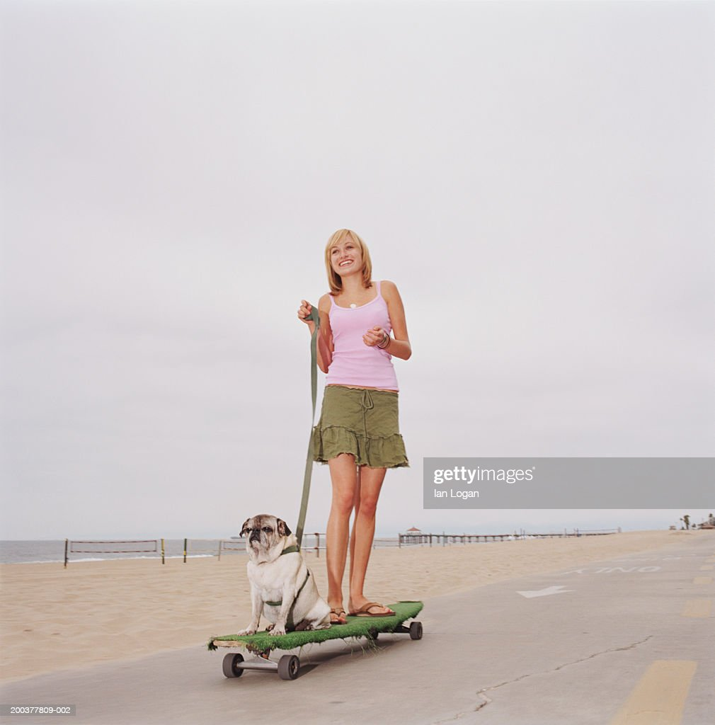 Young woman and pug on longboard skateboard on footpath at beach : Stock Photo