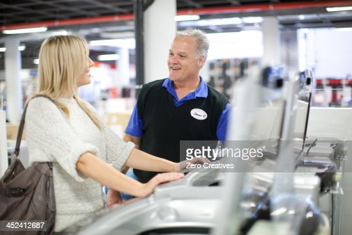 Young woman and salesman negotiating in showroom