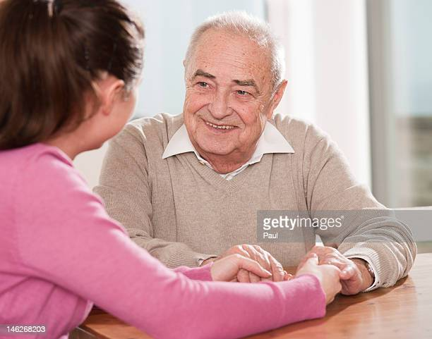 Young woman and senior man sitting hand in hand at table