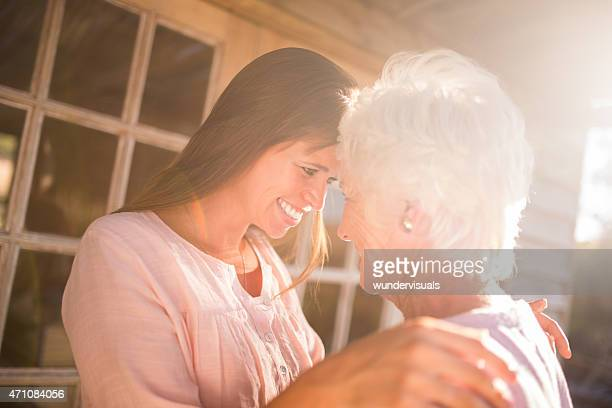 Young woman and senior mother smiling outdoors with sun flare