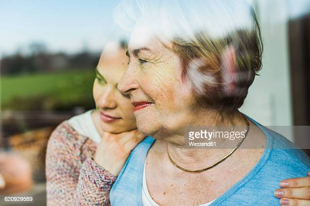Young woman and senior woman behind windowpane