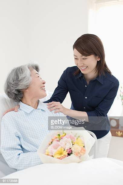 Young woman and senior woman in bed smiling at each other