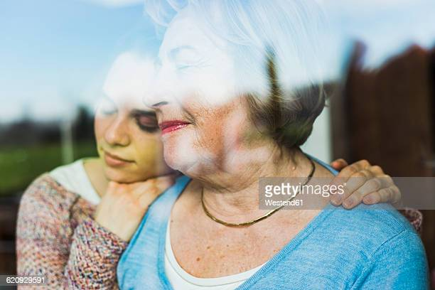 Young woman and senior woman with closed eyes behind windowpane