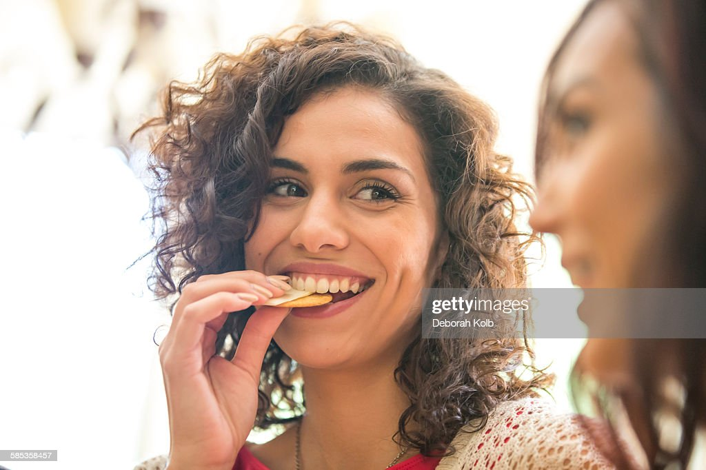 Young woman and sister snacking on cheese and biscuits