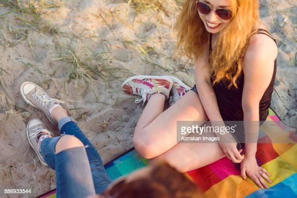 Young woman and teenage girl (16-17) sitting on blanket