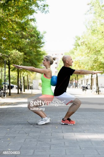 Young woman and trainer using exercise ball in park