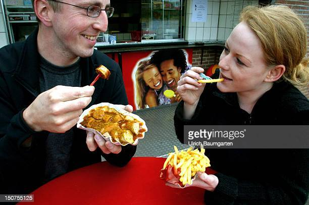 Young woman and young man eating French fries and Curry sausage at a snack booth