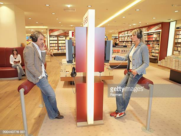 Young woman and young man wearing headphones in book shop