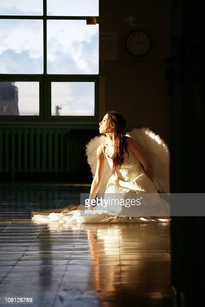 Giovane donna seduta sul pavimento angelo